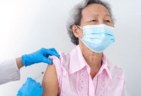 Older, asian woman getting COVID-19 shot